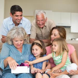 Multigenerational family opening a gift together